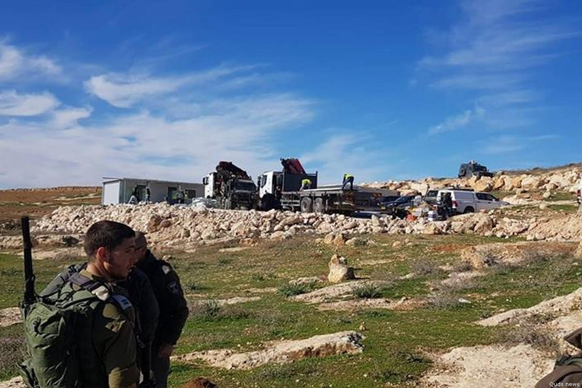 Israeli soldiers watch on as a school in West Bank is demolished on 5 December 2018 [Quds News/Facebook]