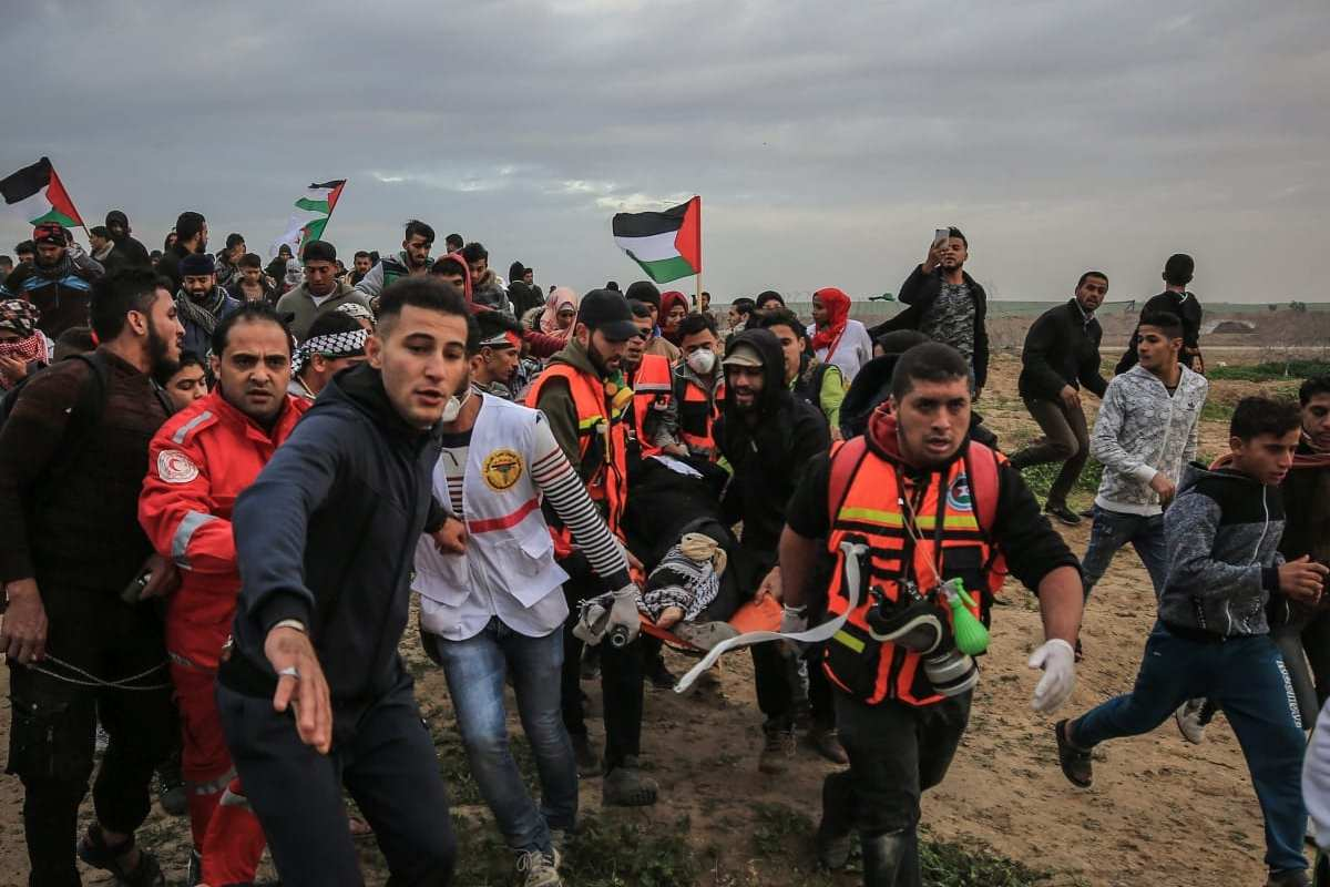"""A Palestinian is being carried away after being injured by Israeli forces during a protest within the """"Great March of Return"""" demonstrations in Shuja'iyya neighborhood of Gaza City, Gaza on December 07, 2018. ( Ali Jadallah - Anadolu Agency )"""