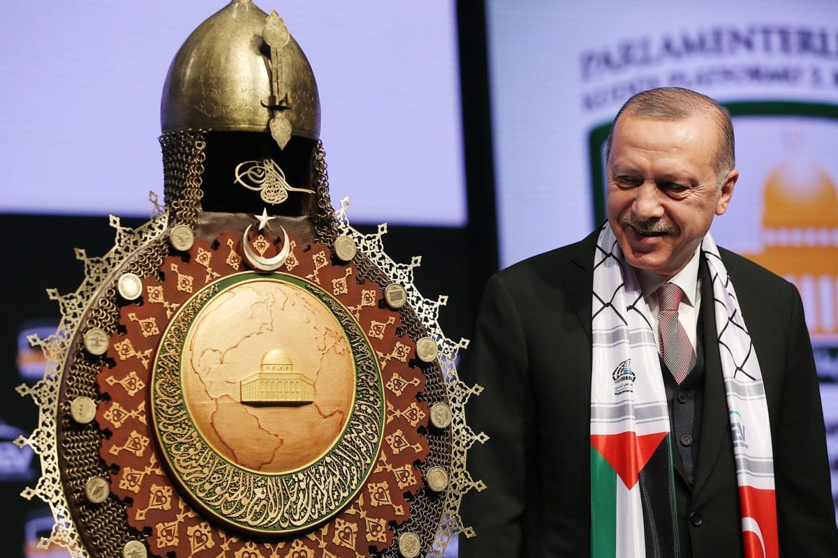 Turkish President Recep Tayyip Erdogan looks at his gift given by Justice and Development (AK) Party's Istanbul Deputy Nureddin Nebati (not seen) during the 2nd Conference of Inter-parliamentary platform on Jerusalem in Istanbul, Turkey on December 14, 2018. ( Murat Kula - Anadolu Agency )