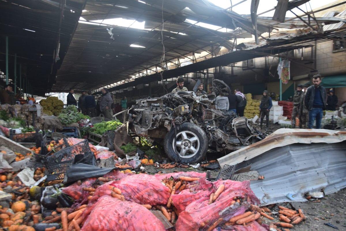 Syrians inspect a car after a car bombing targeted a marketplace in Afrin, Syria on 16 December 2018 [Münib Teym/Anadolu Agency]