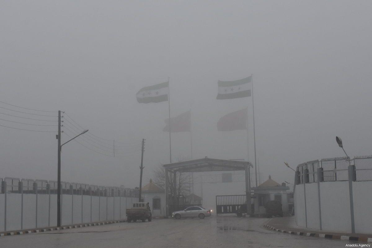 Syrian flag is seen at the Syria -Turkey border gate in Azez as the city is under heavy fog in Aleppo, Syria on December 19, 2018. ( Samer Owaid - Anadolu Agency )