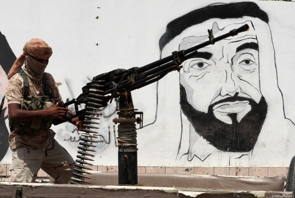 A soldier loyal to the Saudi and UAE-backed government, manning a machin gun mounted on a vehicle passing by a mural depicting the late UAE founder and president Sheikh Zayed bin Sultan al-Nahyan, along a street in the southeastern port city of Mukalla, the capital Hadramawt province on 8 August 2018 (Photo by KARIM SAHIB/AFP/Getty Images)