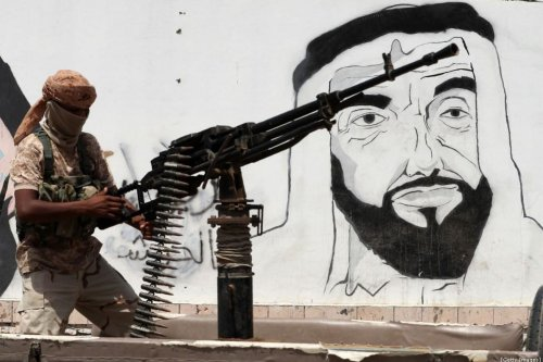 A soldier loyal to the Saudi and UAE-backed government, manning a machine gun mounted on a vehicle passing by a mural depicting the late UAE founder and president Sheikh Zayed bin Sultan al-Nahyan, along a street in the southeastern port city of Mukalla, the capital Hadramawt province on 8 August 2018 [KARIM SAHIB/AFP/Getty Images]