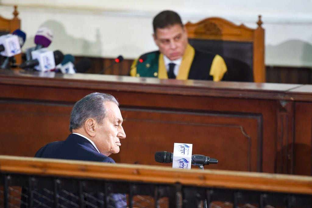 Egyptian judge Mohammed Shirin Fahmi (background) listens to the testimony of former president Hosni Mubarak (front), who was ousted following a popular uprisal in 2011, during a session in the retrial of members of the now-banned Muslim Brotherhood over charges of plotting jailbreaks and attacks on police during the 2011 uprising, at a make-shift courthouse in southern Cairo on December 26, 2018. (Photo by MOHAMED EL-SHAHED/AFP/Getty Images)