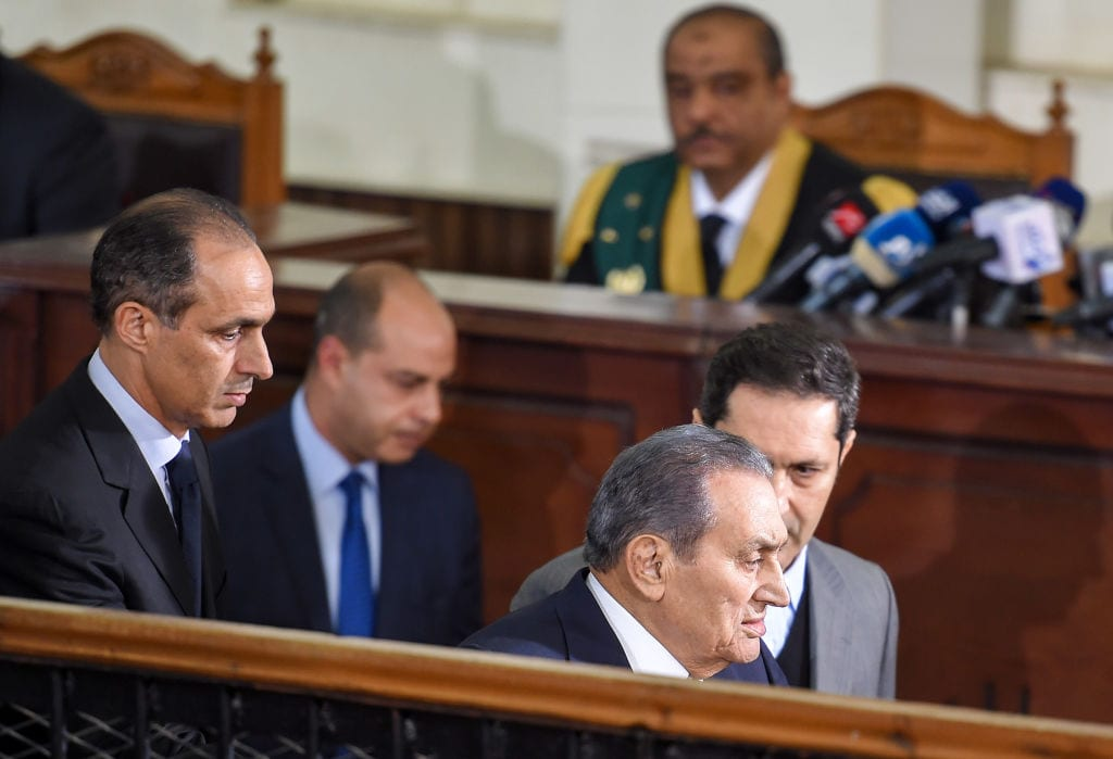 Former Egyptian president Hosni Mubarak (C, front), who was ousted following a popular uprisal in 2011, is escorted by his two sons Alaa (C, behind) and Gamal (L) as he testifies during a session in the retrial of members of the now-banned Muslim Brotherhood over charges of plotting jailbreaks and attacks on police during the 2011 uprising, at a make-shift courthouse in southern Cairo on December 26, 2018. (Photo by MOHAMED EL-SHAHED / AFP / Getty Images)