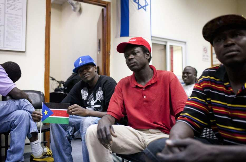 A South Sudanese refugee holds up his national flag as he is held alongside other refugees at a detention centre in Holon, south of Tel Aviv, on June 11, 2012. (Photo by OREN ZIV/AFP/GettyImages)