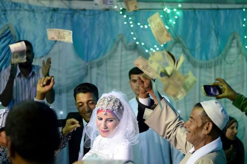 A bride and groom are showered with money as they dance during a wedding in the Egyptian Nile Delta province of al-Minufiyah on May 20, 2016. (Photo by MOHAMED EL-SHAHED/AFP/Getty Images)