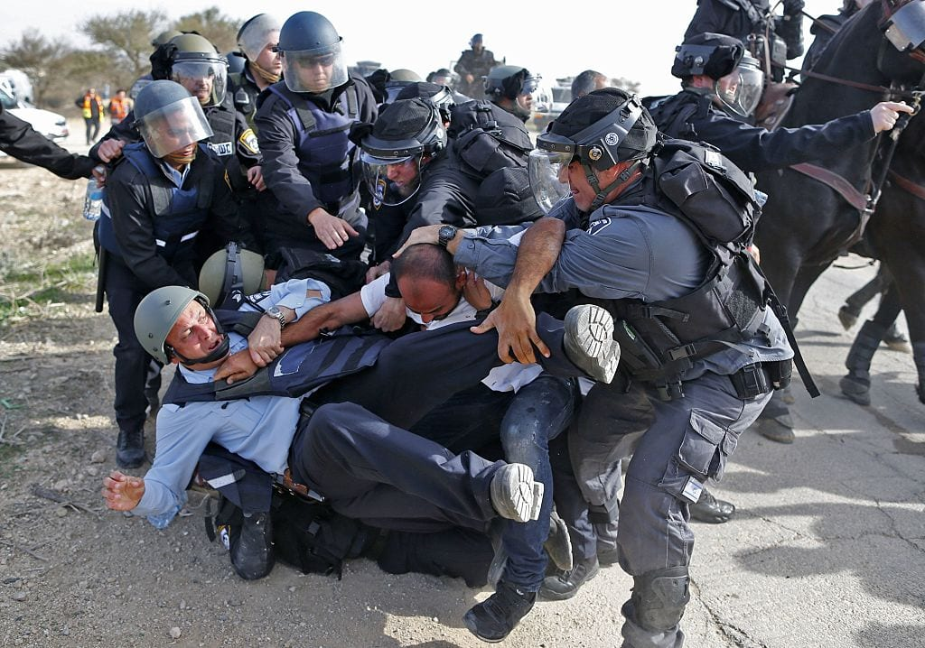 Israeli policemen detain a Bedouin man during clashes that followed a protest against home demolitions on January 18, 2017 in the Bedouin village of Umm al-Hiran, which is not recognized by the Israeli government, near the southern city of Beersheba, in the Negev desert. (Photo AHMAD GHARABLI/AFP/Getty Images)