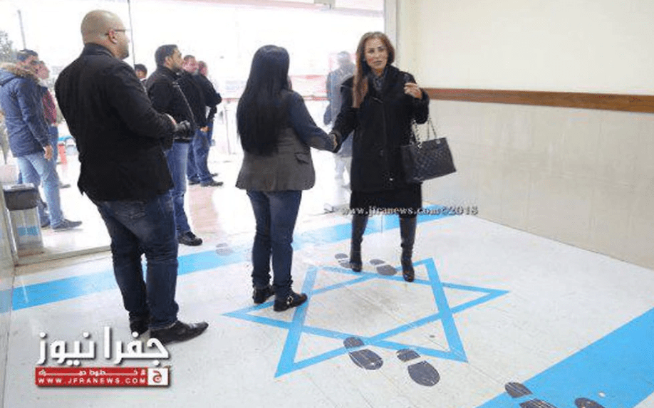 The Jordanian Information and Government Spokeswoman, Jumana Ghunaimat, arrives at the Jordanian Trade Union Headquarters in Amman and steps on a drawing of the Israeli flag, on December 27, 2018 [jfranews.com.jo]