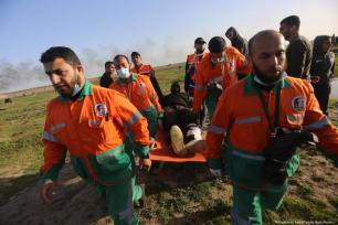 Medics carry injured Palestinians after Israeli forces fired at protesters during the Great March of Return on 25 January 2019 [Mohammed Asad/Middle East Monitor]