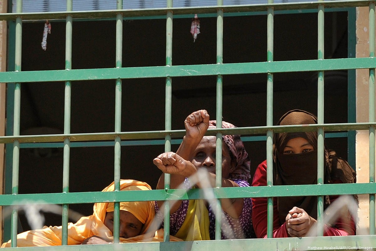 Migrants glance out of the windows at a detention centre on 19 July 2013 [Matthew Mirabelli/AFP/Getty Images]