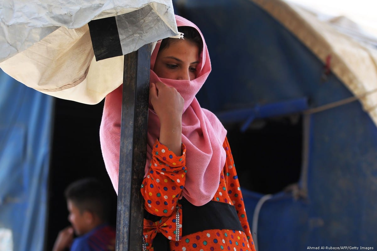 A displaced Iraqi girl stands near a camp in Iraq on 24 April 2018 [Ahmad Al-Rubaye/AFP/Getty Images]