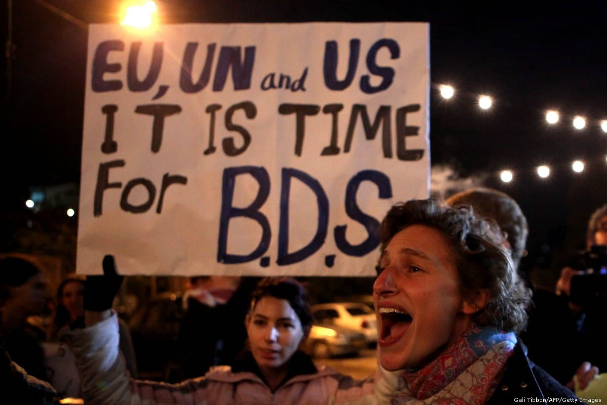 Demonstrators hold a placard urging the international community to support the Boycott, Divestment, and Sanctions (BDS) campaign [Gali Tibbon/AFP/Getty Images