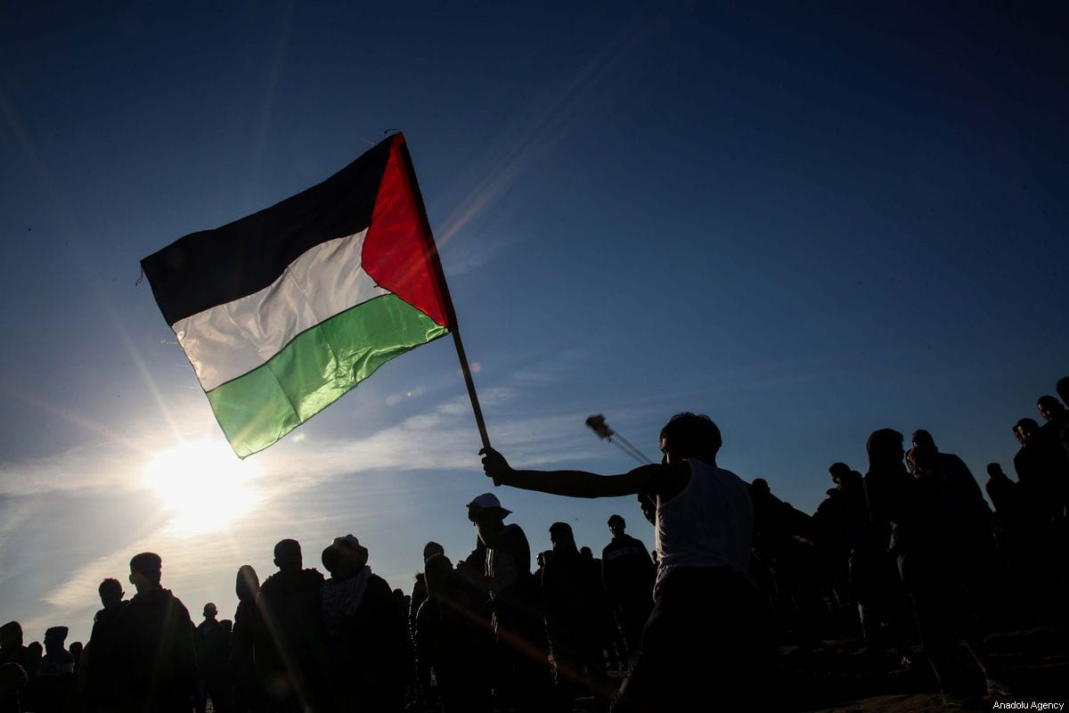 "A Palestinian throws rock as he holds a Palestinian flag in response to Israeli forces' intervention during a protest within the ""Great March of Return"" demonstrations at Al Bureij Refugee Camp near Gaza-Israel border in Gaza City, Gaza on January 11, 2019. ( Hassan Jedi - Anadolu Agency )"