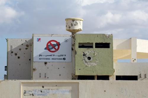 A rocket-riddle building with a sign in Arabic calling for people to stay away from non-exploded devices is seen in Tripoli, Libya on 9 November 2018 [MAHMUD TURKIA/AFP/Getty Images]