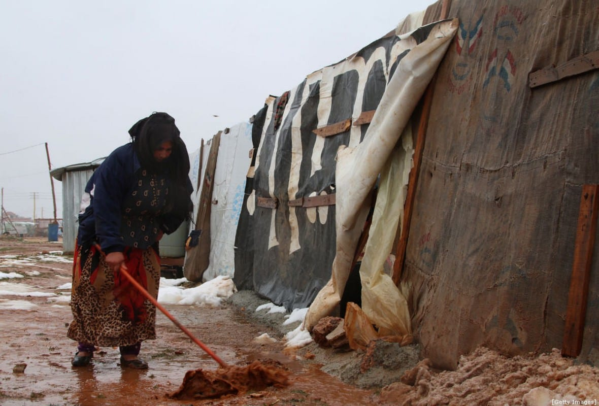 A Syrian refugee shovels mud in front of a makeshift shelter in an unofficial camp for Syrian refugees in Iaat in Lebanon's Bekaa valley, following heavy rain storms on January 8, 2019. (Photo by/ AFP/Getty Images)