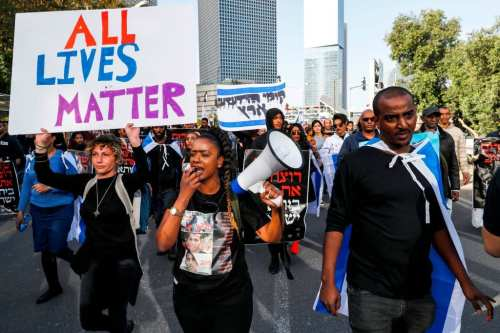 Israelis of Ethiopian origin chant slogans and carry signs as they block a highway in the Israeli city of Tel Aviv on 30 January 2019, during a protest against police violence. [JACK GUEZ/AFP/Getty Images]