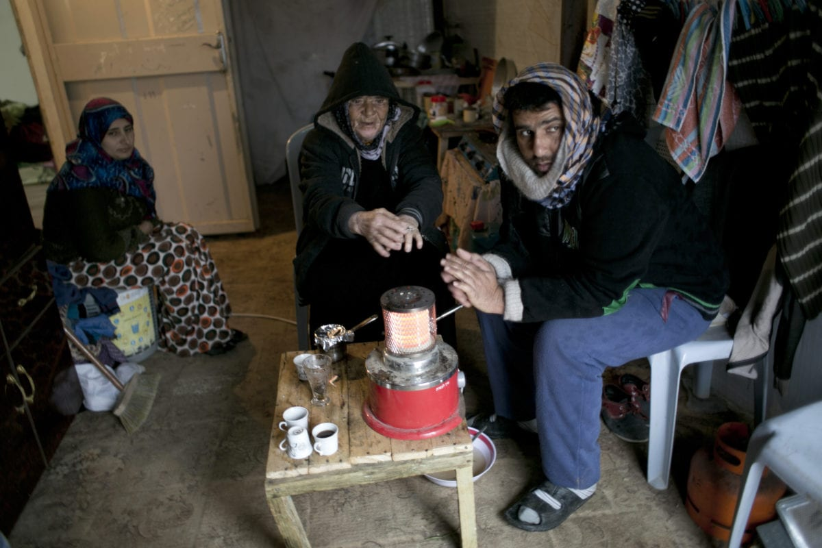 A Palestinian family sits around a heater in their temporary housing during a winter storm in the southern Gaza Strip town of Khan Younis, Palestine on January 25, 2016 [SAID KHATIB/AFP/Getty Images]