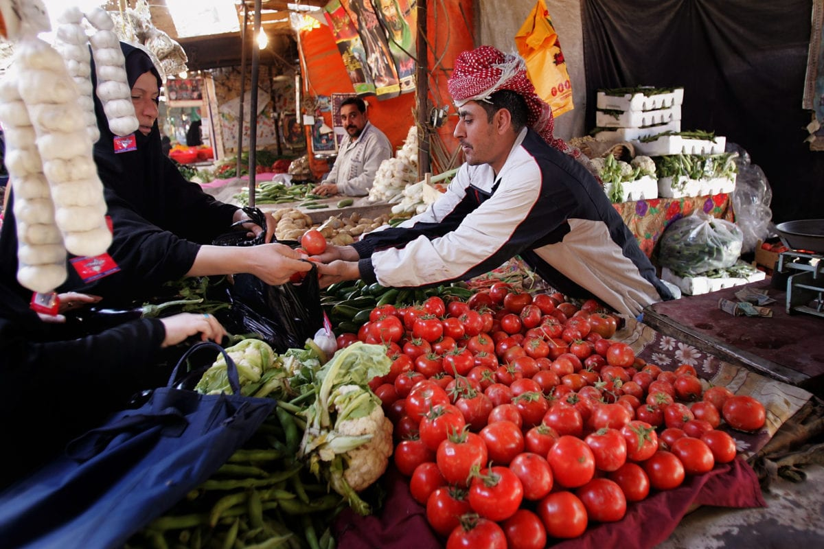 An Iraqi grocer puts tomato in a plastic bag as he serves customers on March 3, 2008 in Baghdad, Iraq [Wathiq Khuzaie /Getty Images]