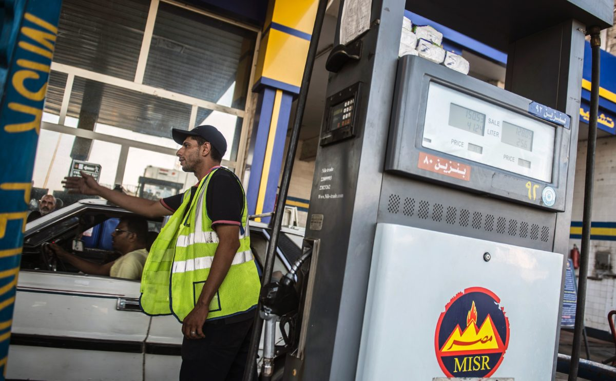 A worker gesturing for cars to move as others fill up a at a petrol station in Cairo, Egypt [KHALED DESOUKI/Getty Images]