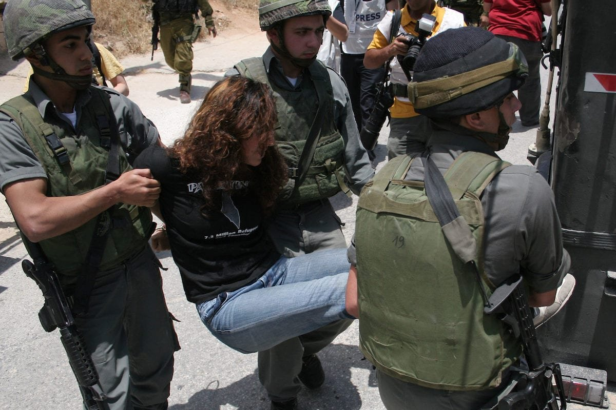 Israeli soldiers arrest a woman protester during a demonstration by Palestinian, Israeli and foreign activists against Israel's controversial separation barrier which crosses the Palestinian territories in the West Bank town of Beit Jala, near the biblical town of Bethlehem, on 27 June 2010 [Mamoun Wazwaz/Apaimages]