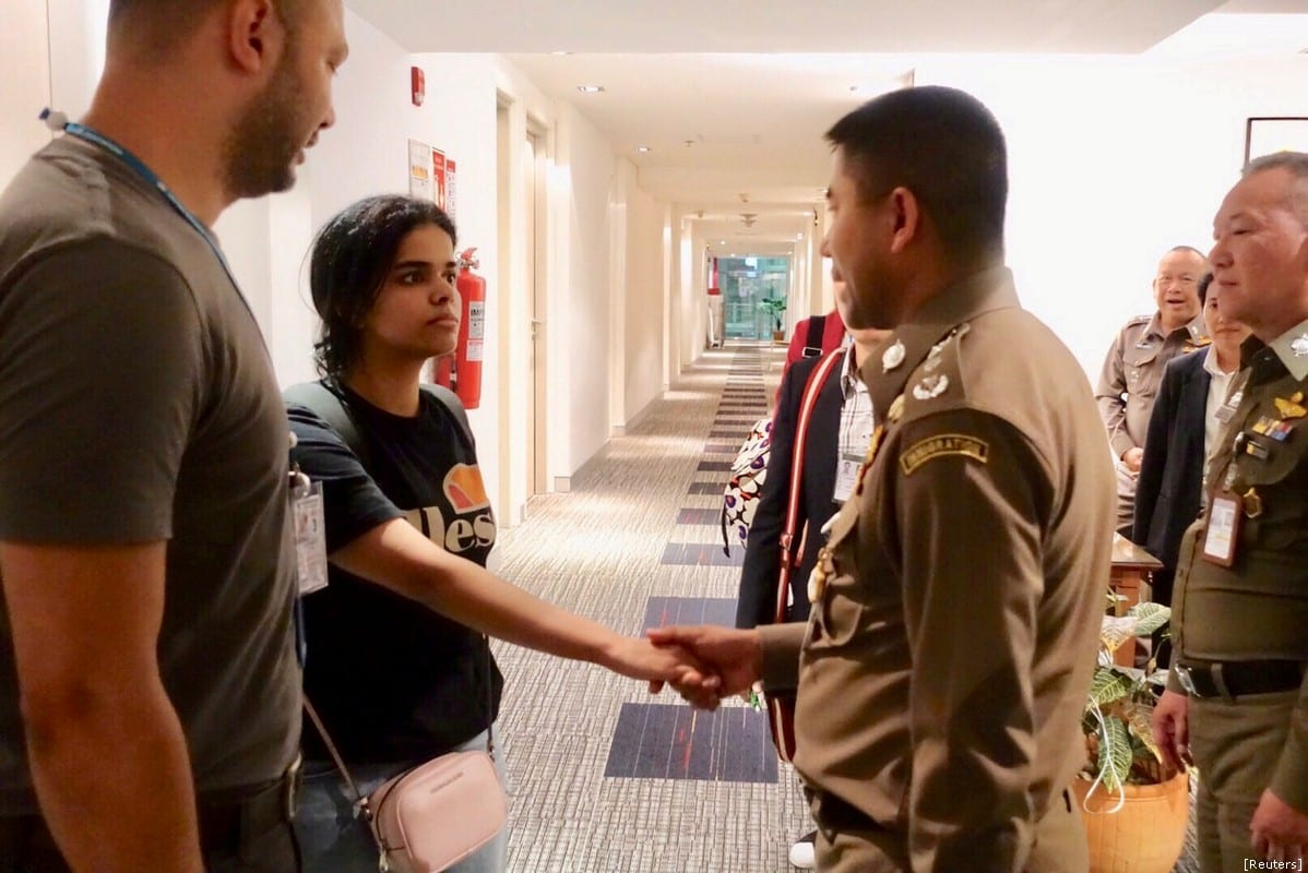 Saudi teen Rahaf Mohammed al-Qunun is greeted by Thai immigration authorities at a hotel inside Suvarnabhumi Airport in Bangkok, Thailand January 7, 2019. [Reuters]
