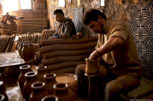 "Turkish craftsmen Yenal Yorgun (front) and Mustafa Alkan (rear) make clay pots. Yorgun and Alkan use the red clay collected from Kizilirmak (""red river"") and sell their finish products to Saudi Arabia, Dubai, Qatar in Cappadocia's Avanos district, Nevsehir, Turkey on 5 February 2019 [Behçet Alkan/Anadolu Agency]"