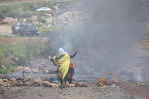 A Palestinian protester uses a slingshot to throw stones to Israeli forces during a protest against excavation works on Palestinian lands, near an illegal Israeli settlement, in the town of al-Mughayyir, West Bank on February 01, 2019 [Issam Rimawi / Anadolu Agency]