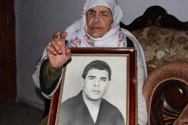 Mother of 51-year-old Palestinian prisoner, Faris Baroud holds his photo - [Facebook]