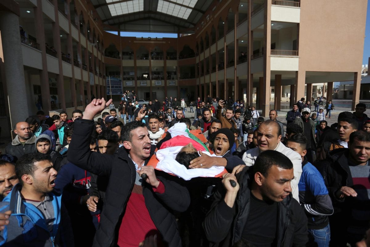 """Mourners carry the body of Hassan Shalabi, 14, who was killed after Israeli soldiers' intervention in a """"Great March of Return"""" demonstration on February 8, 2019. [Ashraf Amra - Anadolu Agency]"""