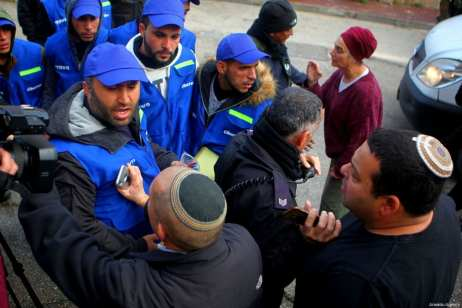 Jewish settlers react to members of the Palestinian Youth Against Settlements (YAS) activists as they gather in Hebron, West Bank on February 10, 2019. The YAS activists have dressed up similar to the Temporary International Presence in Hebron (TIPH), established after a massacre of Palestinians in 1994, following Israel's decision not to renew the mandate of the monitoring group in West Bank city [Mamoun Wazwaz / Anadolu Agency]