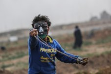 """Palestinians use sling shot to throw rocks as Israeli forces clash with them during a """"Great March of Return"""" demonstration at Huzaa district of Khan Yunis, Gaza on February 15, 2019. ( Mustafa Hassona - Anadolu Agency )"""
