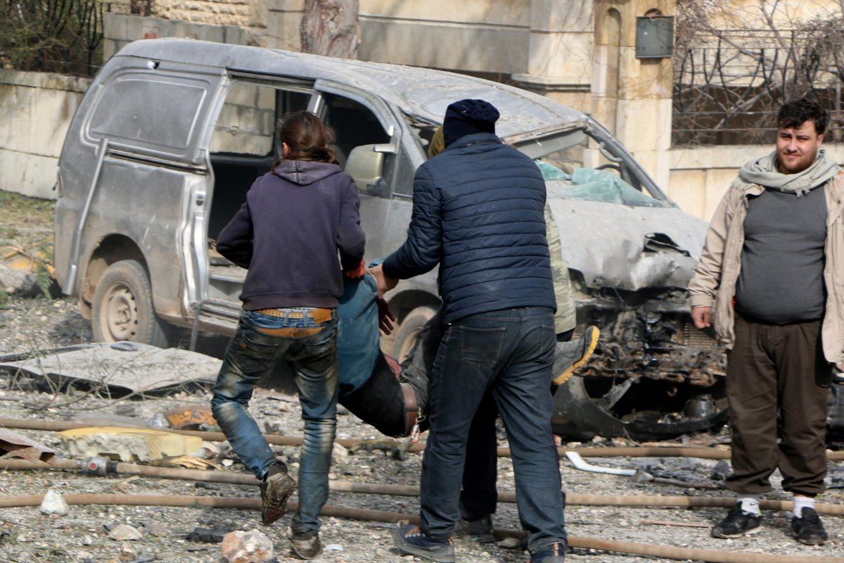 People carry a body of a man around the wreckage site after the consecutive bomb attacks with two bomb-laden vehicles in Idlib city centre, Syria on 18 February, 2019 [Ahmet Rehhal/Anadolu Agency]
