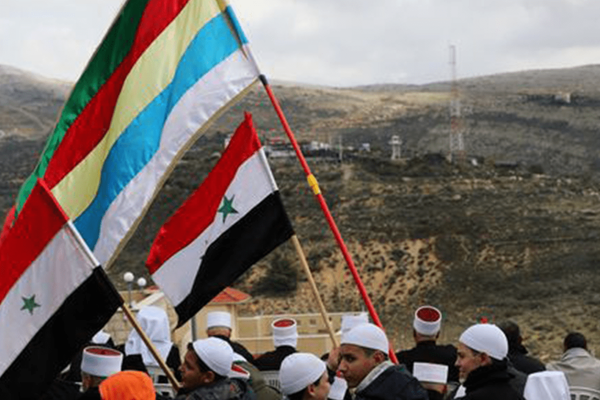 Members of the Druze community holds Syrian and Druze flags as they sit facing Syria [Twitter]