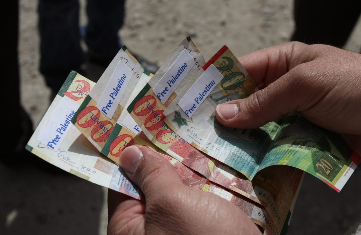 "A Palestinian man holds News Israeli Shekels' bills marked with stickers reading ""Free Palestine"" on March 7, 2011 in the West Bank city of Ramallah, as part of a campaign aimed to peacefully express opposition to Israel's occupation. [ABBAS MOMANI/AFP/Getty Images]"