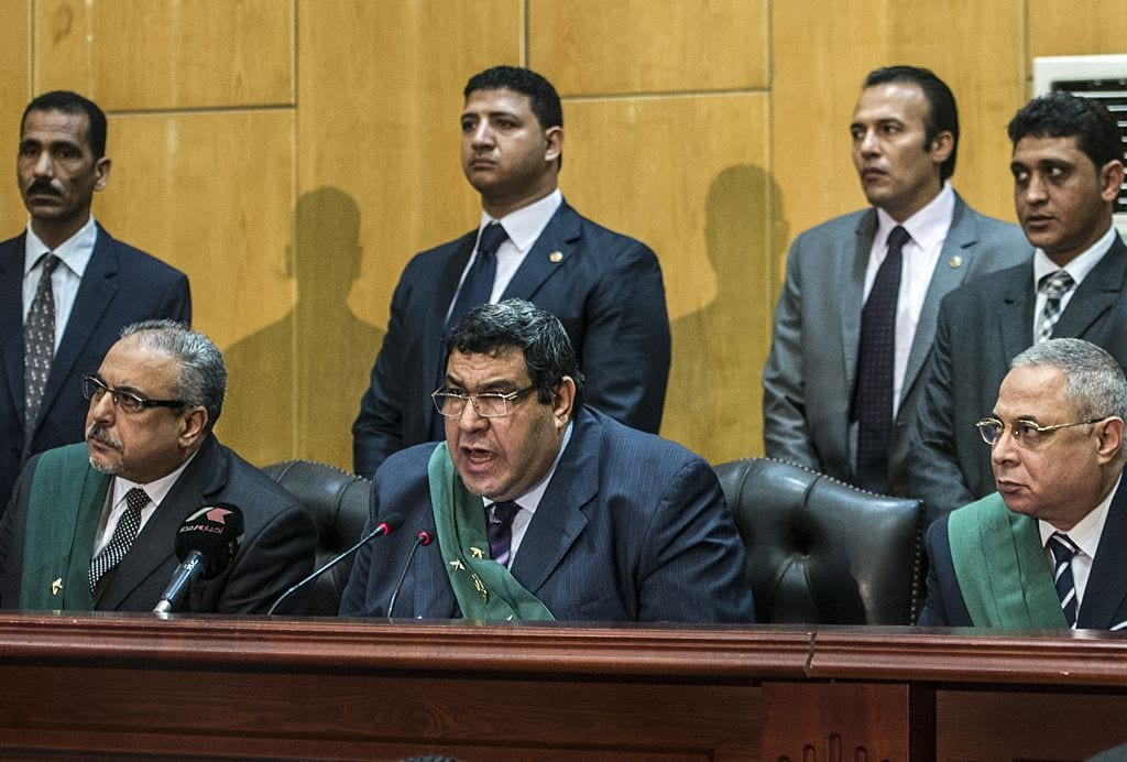 Egyptian judge Shaban el-Shamy (C) reads out the verdict sentencing deposed Islamist president Mohamed Morsi and more than 100 other defendants to death at the police academy in Cairo on 16 May 2015. [KHALED DESOUKI/AFP/Getty Images]