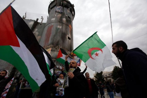 Palestinian protestors chant slogans and wave the national flag and the Algerian flag during a demonstration in the West Bank city of Bethlehem on 29 December 2017, following the weekly Muslim Friday prayers. [MUSA AL SHAER/AFP/Getty Images]