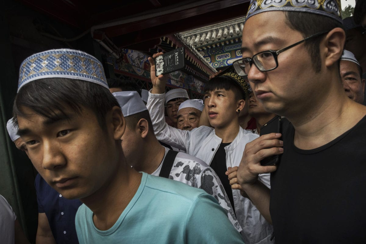 Chinese Muslim men leave following Eid al-Fitr prayers marking the end of the holy fasting month of Ramadan at the historic Niujie Mosque on June 16, 2018 in Beijing, China [Kevin Frayer/Getty Images]