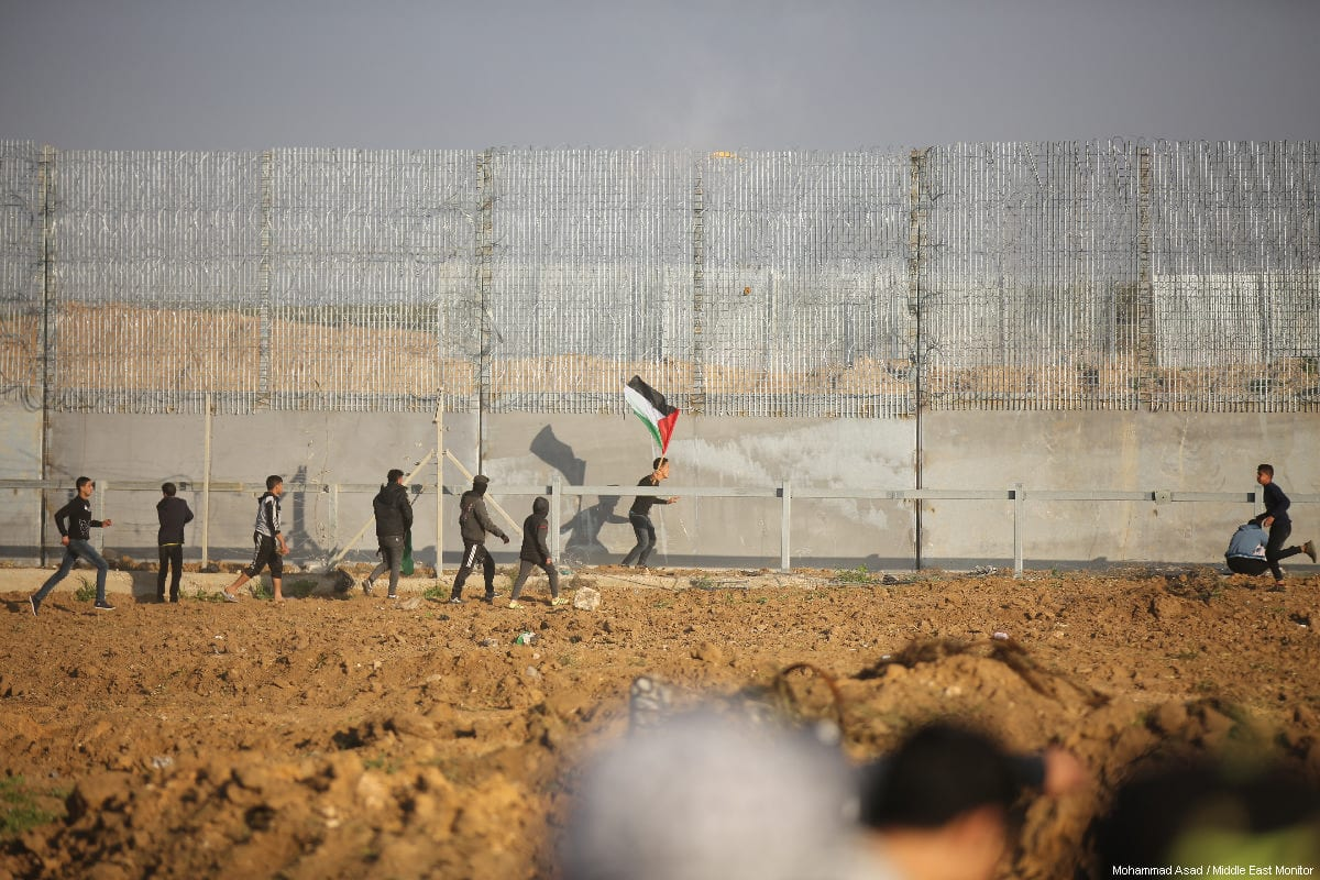 """Palestinian protestors seen near a section of the Israeli border fence, during a weekly """"Great March of Return"""" demonstration near the Israel-Gaza border, on March 22, 2019 [Mohammad Asad / Middle East Monitor]"""