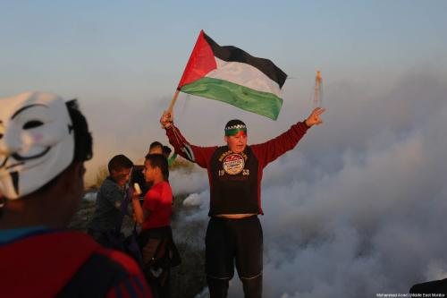 """Palestinian protestor seen during a weekly """"Great March of Return"""" demonstration near the Israel-Gaza border, on March 22, 2019 [Mohammad Asad / Middle East Monitor]"""