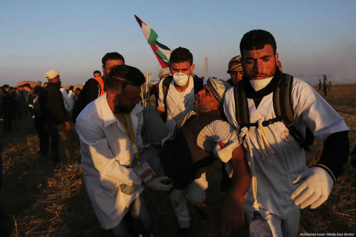 """Palestinian medics carry away an injured protestor during a weekly """"Great March of Return"""" demonstration near the Israel-Gaza border, on March 22, 2019 [Mohammad Asad / Middle East Monitor]"""