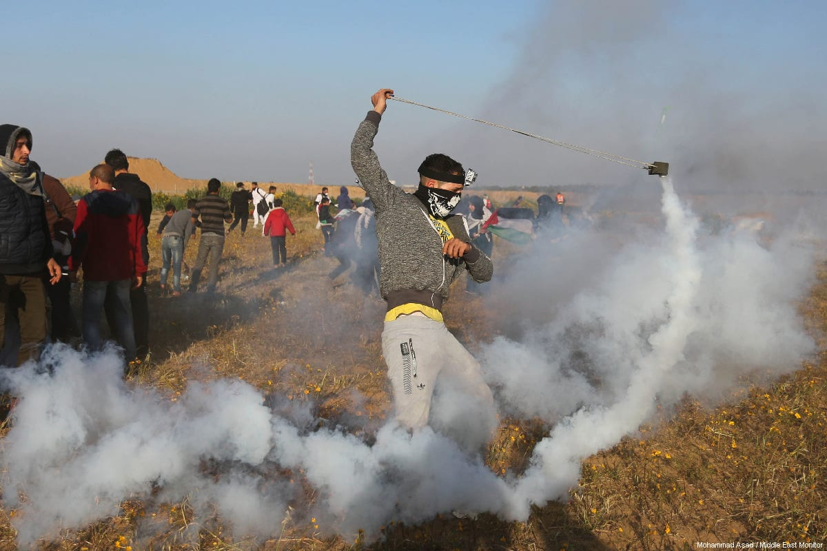 "A Palestinian protestor tries to use a sling-shot to return a tear gas canister fired by Israeli forces, during a weekly ""Great March of Return"" demonstration near the Israel-Gaza border, on March 22, 2019 [Mohammad Asad / Middle East Monitor]"