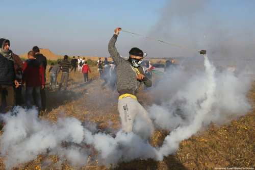 """A Palestinian protestor tries to use a sling-shot to return a tear gas canister fired by Israeli forces, during a weekly """"Great March of Return"""" demonstration near the Israel-Gaza border, on March 22, 2019 [Mohammad Asad / Middle East Monitor]"""