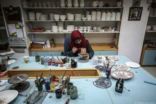 Inside a small pottery manufacturer, the place is silent; three deaf and dumb people work with extreme precision and focus. [Ali Jadallah/Anadolu Agency]