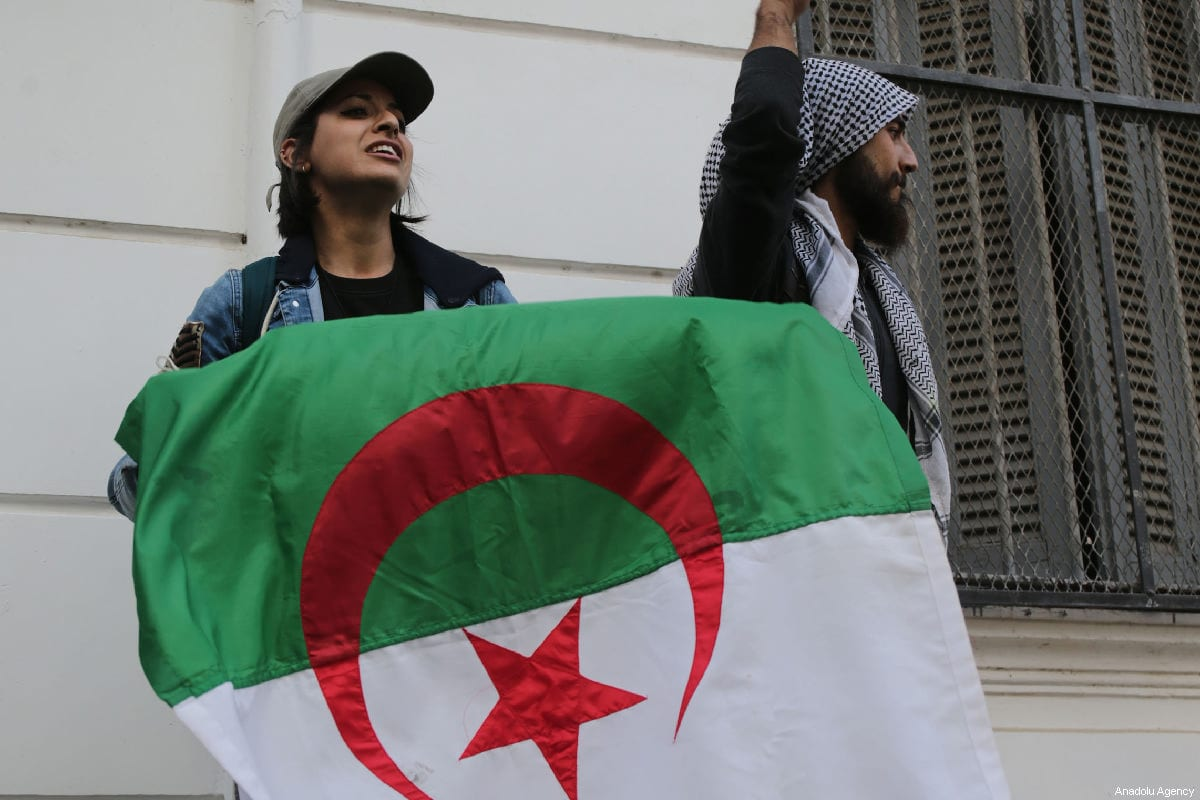 Protesters in Algeria hold an Algerian flag on 26 February 2019. [Farouk Batiche/Anadolu Agency]