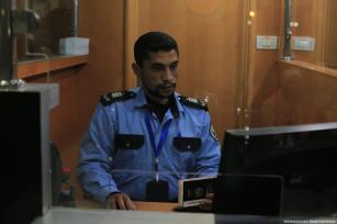 A Palestinian border control officer seen at a immgration desk on the Palestinian side of the Rafah crossing, in Rafah, Gaza on March 03, 2019 [Mohammad Asad / Middle East Monitor]