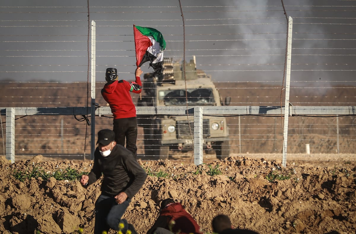 "Palestinian protesters climb wire fences during ""Great March of Return"" demonstration near Israel-Gaza border, in east of Shuja'iyya neighborhood, Gaza City, Gaza on 8 March, 2019 [Ali Jadallah/Anadolu Agency]"