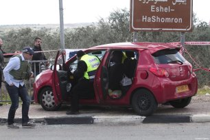 Israeli security forces take security measures at the crime scene and inspect the car which was used in the attack after an Israeli was killed and three were wounded in a shooting attack near Ariel settlement in West Bank on March 17, 2019 [Nedal Eshtayah / Anadolu Agency]