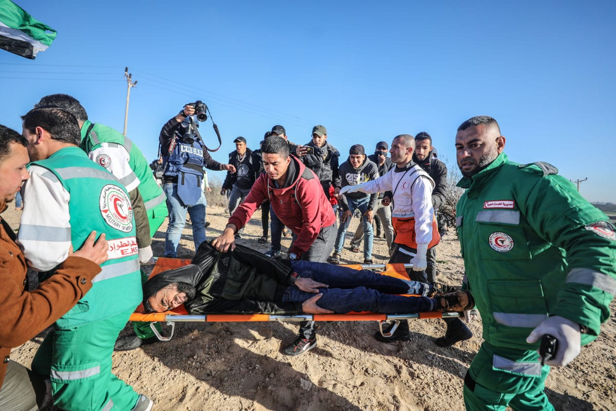 An injured Palestinian is being carried away with health care members during a maritime protest against Israel's ongoing blockade of Gaza on the strip's northern coast, in Beit Lahia, Gaza on March 19, 2019. [Mustafa Hassona - Anadolu Agency]