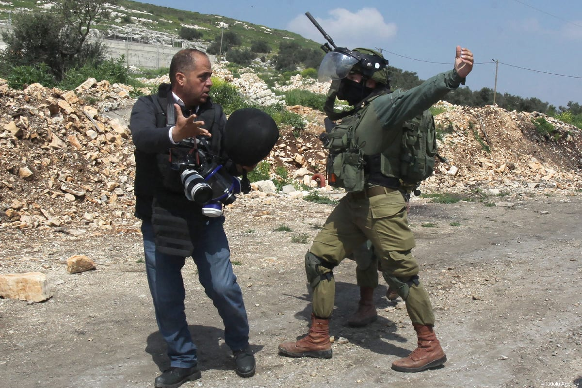 An Israeli soldier attacks AFP'S photo journalist Jafer Eshtayah during a protest against building of illegal settlements and the separation wall at the Kafr Qaddum village of Nablus, West Bank on March 22, 2019 [Nedal Eshtayah / Anadolu Agency]